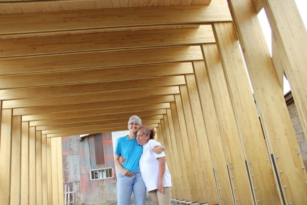 La directora del SIFAIS, Maris Stella Fernández, junto con la lideresa comunal de La Carpio, Alicia Avilés. La estructura donde se alberga el SIFAIS, un centro cultural, está construida en su mayoría con madera.